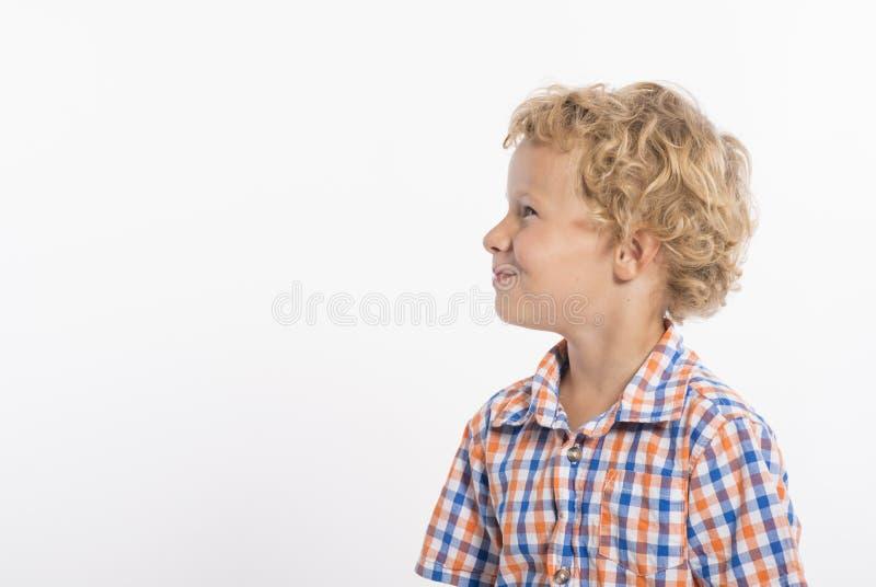 Profil des gelockten behaarten, blonden Jungen auf weißem Hintergrund stockfotos