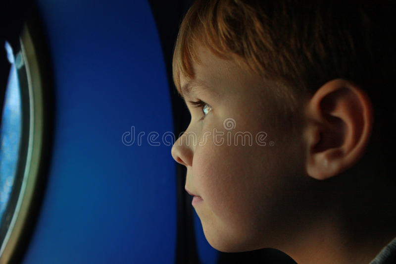 Profil des Jungen, das durch Öffnung schaut stockfotos