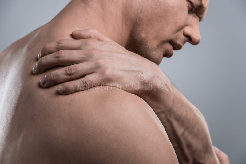 Profil des jungen hemdlosen Mannes mit den Schulterschmerz stockbilder