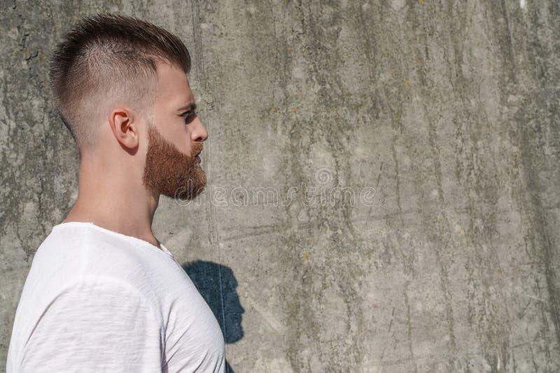 Profil des jungen schönen bärtigen Kerls, der draußen gegen moderne Dachbodenwand des grauen modernen Dachbodens mit ruhigem Gesi lizenzfreie stockbilder