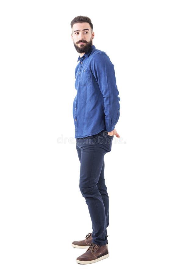 Profil des kühlen jungen modischen Mannes im blauen Denimhemd, das zurück über der Schulter schaut stockbild