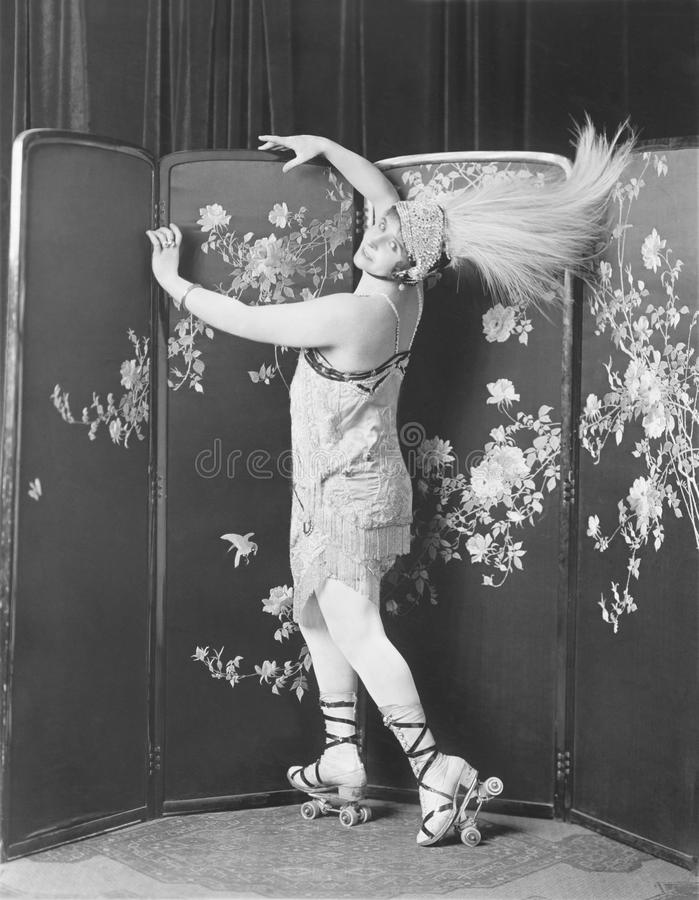 Profil des patins de rouleau de port de jeune femme utilisant un chapeau de plume (toutes les personnes représentées ne sont pas  photographie stock libre de droits