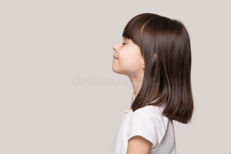 Profil des ruhigen kleinen Mädchens lokalisiert auf grauem Studiohintergrund stockbild