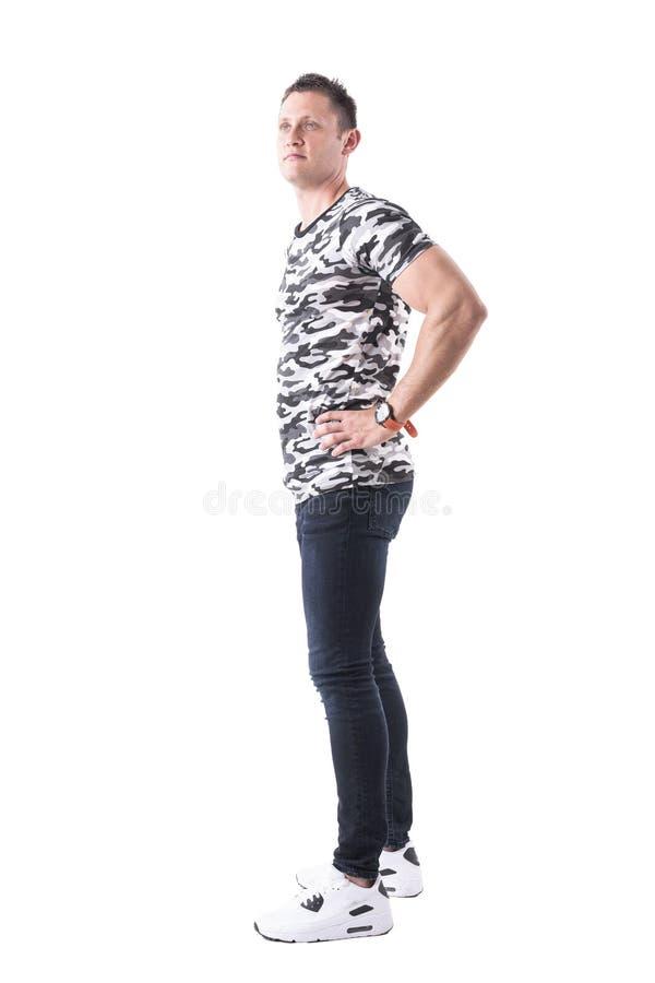 Profil des zufälligen Mannes des überzeugten Sports im Militärhemd mit den Händen auf den Hüften, die oben schauen lizenzfreie stockfotos