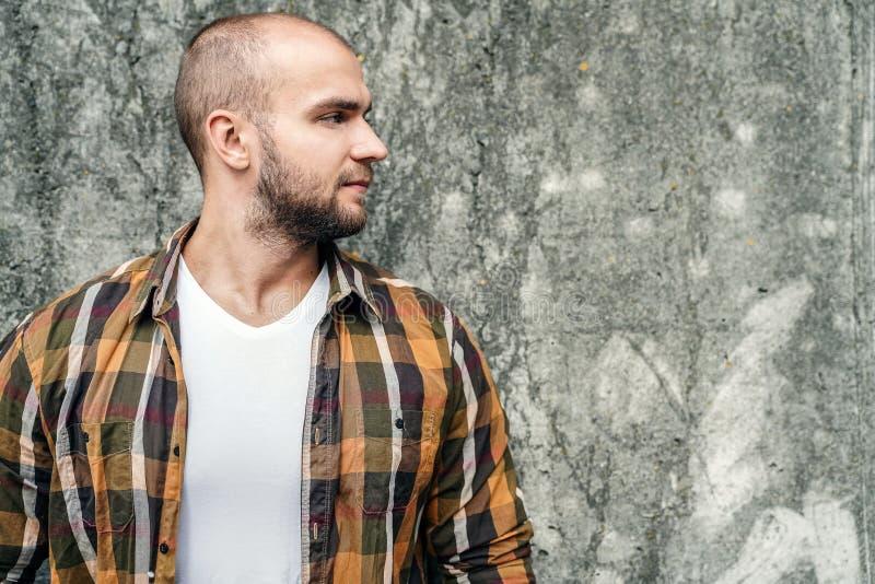 Profil du jeune type barbu audacieux beau se tenant dehors contre le mur moderne gris de grenier regardant de côté avec le visage image stock