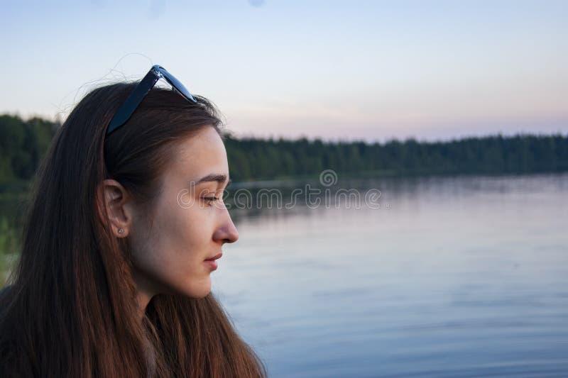 Profil dziewczyn spojrzenia przy wodą Jezioro fotografia royalty free