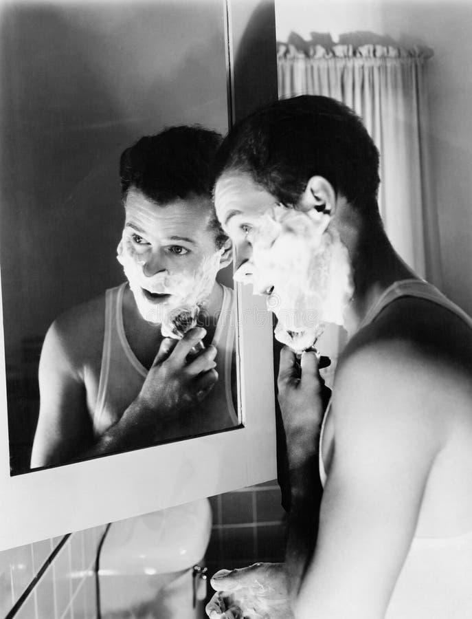 Profil eines jungen Mannes vor einem Spiegel in einem Badezimmerrasieren (alle dargestellten Personen sind nicht längere lebende  stockbilder
