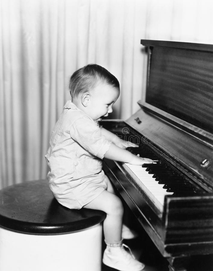 Profil eines kleinen Jungen, der auf einem Schemel sitzt und ein Klavier spielt (alle dargestellten Personen sind nicht längeres  lizenzfreies stockfoto