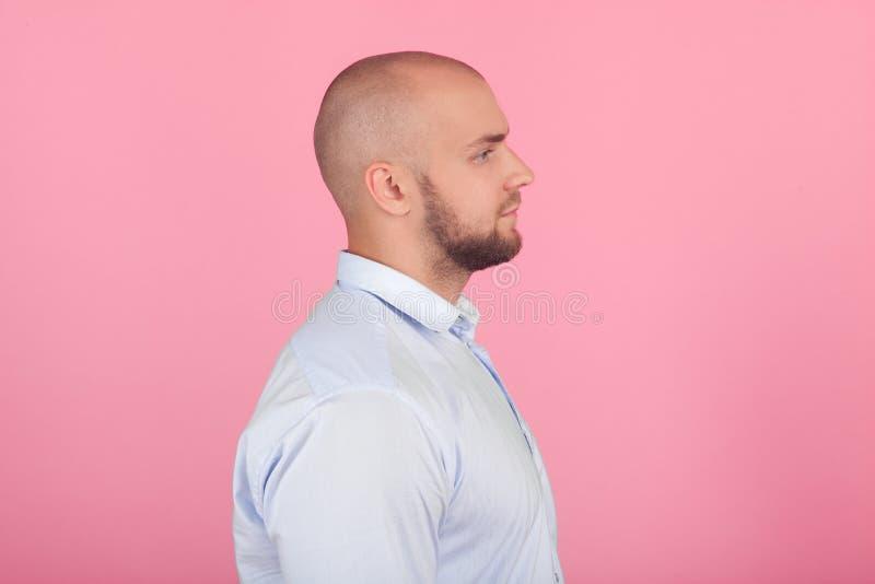 Profil eines sch?nen kahlen Mannes mit einem Bart gekleidet in einem wei?en Hemd St?nde vor dem rosa Hintergrund stockbilder