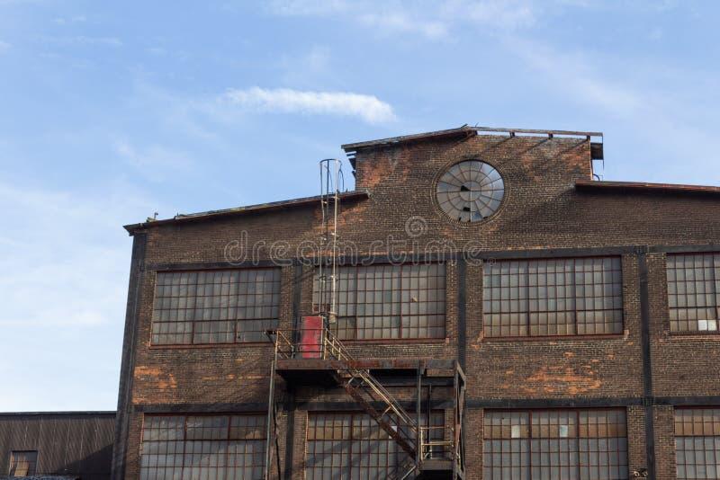Profil eines verlassenen Industriegebäudes, Kreisfenster in der Ziegelsteinfassade lizenzfreies stockfoto