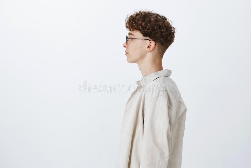 Profil geschossen vom männlichen Freiberufler des stilvollen hübschen jungen Hippies mit gelockter Frisur in den Gläsern, die lin lizenzfreies stockbild