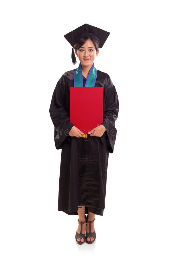 Profil intégral de diplômé féminin dans sa robe scolaire tenant une plaquette rouge, support sur le fond blanc image libre de droits