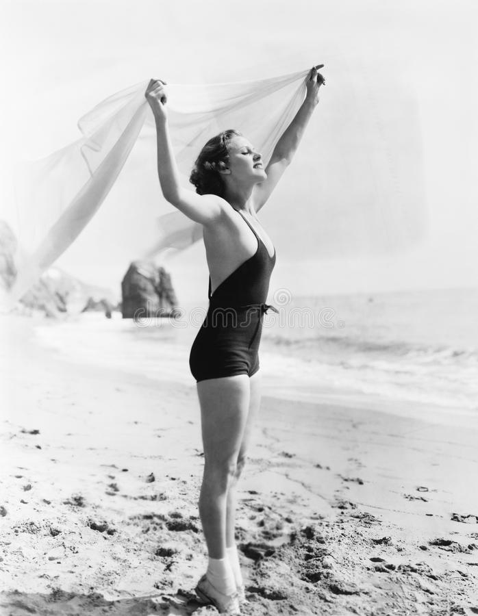 Profil młoda kobieta trzyma up sarong przy plażą (Wszystkie persons przedstawiający no są długiego utrzymania i żadny nieruchomoś obrazy royalty free