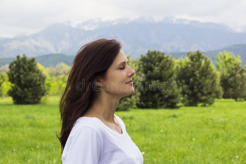 Profil młoda kobieta z oczami zamykał oddychania świeże powietrze w górach obrazy stock