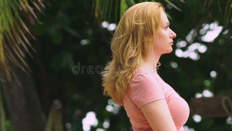Profil piękna blond kobieta która stoi przeciw drzewku palmowemu na wietrznym dniu, patrzeje w kamerę i ono uśmiecha się zdjęcia stock