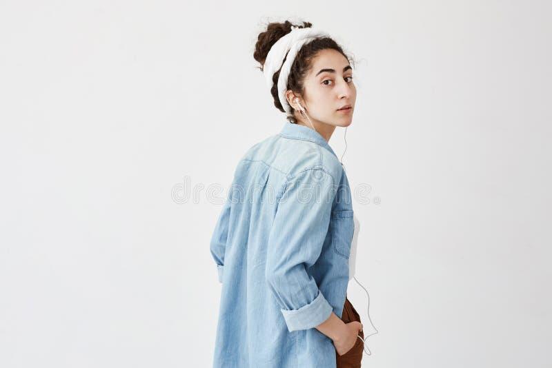 Profil piękna kobieta modela mienia ręka w kieszeniowym słuchaniu muzyki lub audio książka podczas gdy pozujący indoors, z obrazy royalty free