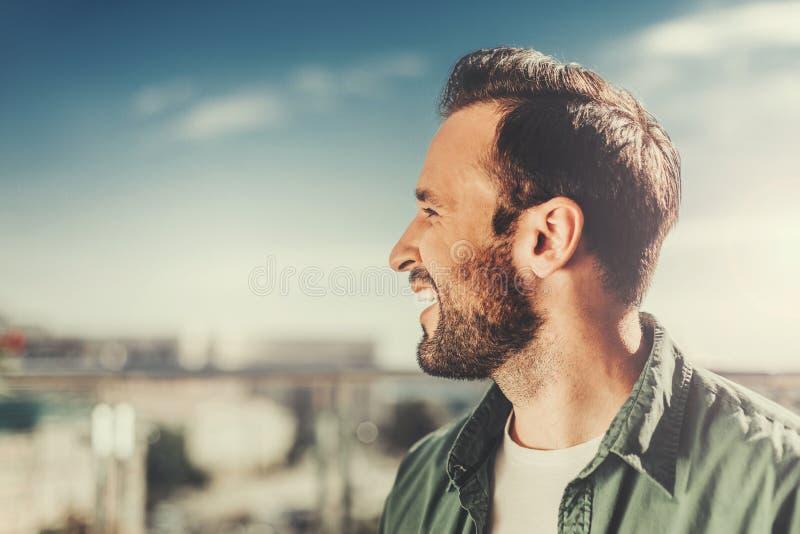 Profil rozochocony brodaty mężczyzna na zamazanym tle zdjęcie royalty free