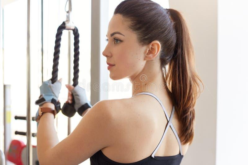 Profil sportowa młoda kobieta opracowywa na stażowym aparacie w gym klasie, patrzeje na boku, trenuje jej ciało, konika ogon,  obraz stock