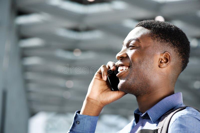 Profil szczęśliwy młody amerykanin afrykańskiego pochodzenia mężczyzna opowiada na telefonie komórkowym obraz royalty free