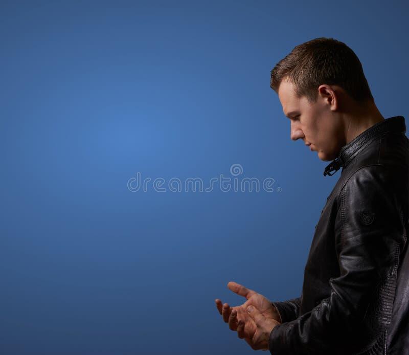 Profil tiró de un hombre joven en el leatherjacket, frotando su mano con el copyspace foto de archivo