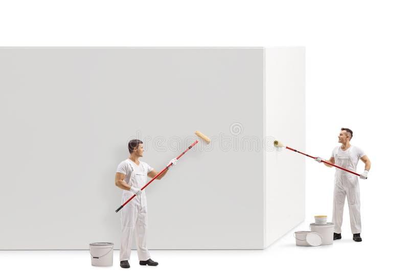 Profil in voller Länge schoss von zwei Malern, die eine Wand malen lizenzfreies stockfoto