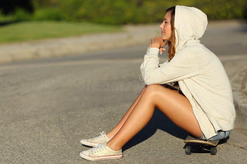 Profil zadumany nastolatek dziewczyny obsiadanie na łyżwie w ulicie obrazy stock