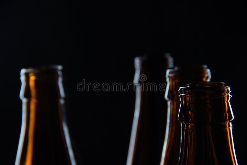 Profila le bottiglie di vetro per la birra su un fondo nero fotografie stock