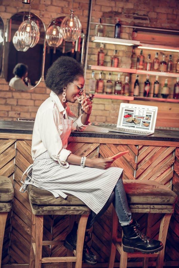 ProfilAfro--amerikan servitris som sitter i stolen nära stångräknare royaltyfria foton