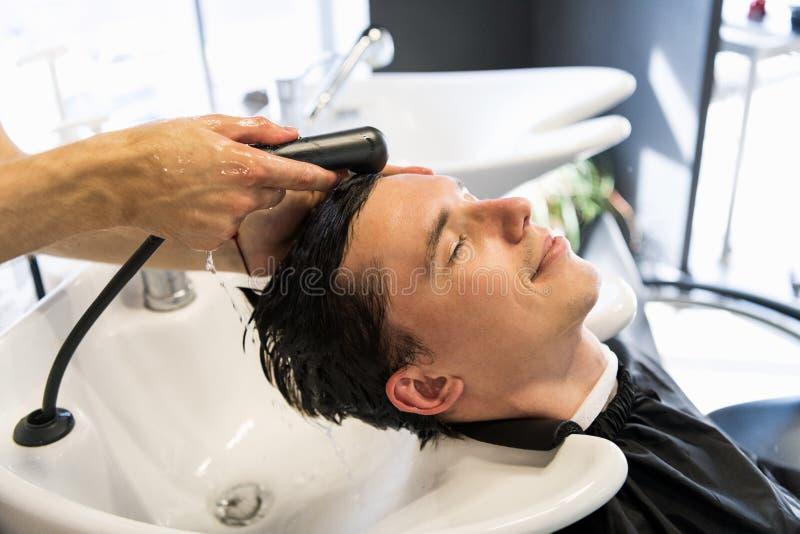 Profilansicht eines jungen Mannes, der sein Haar gewaschen und sein Kopf erhält, massierte in einem Friseursalon stockbilder