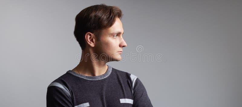 Profilbild av en stilig man isolerad på grå bakgrund royaltyfri foto