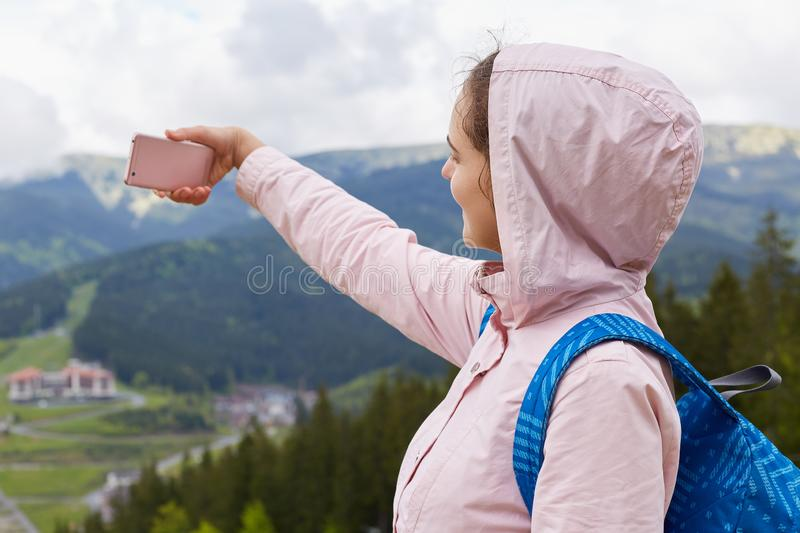 Profile of active traveller taking photo on mountain background, recording video for travel blog, spending time with pleasure on stock photography