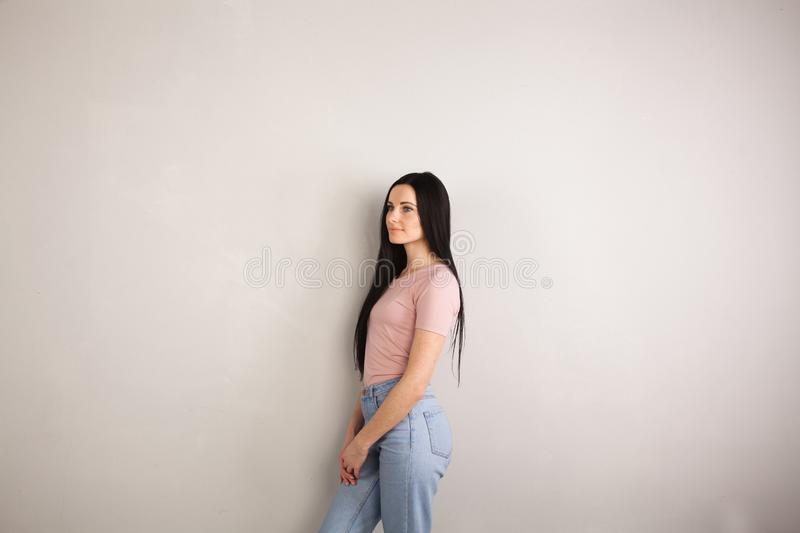 Profile of attractive young brunette woman with long hair standing by the grey background wearing pink shirt and jeans stock images