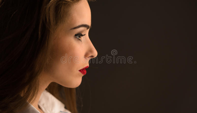 Profile of beautiful lady with long hair in studio royalty free stock photo
