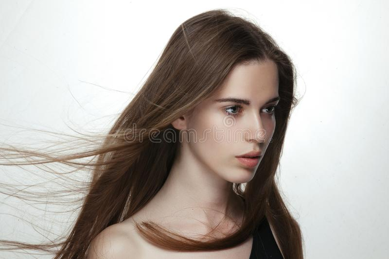 Profile of beautiful sensual girl with long hair in wind, naked shoulders, isoated on white background. Fresh skincare. royalty free stock images
