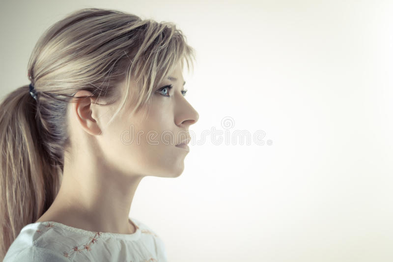Profile of a beautiful serious blond woman stock image