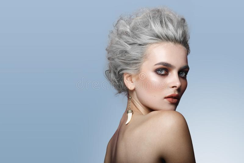 Profile of beautiful young model with gray hairstyle, naked shoulders, makeup, smokey eyes, isolated on blue background. stock photo
