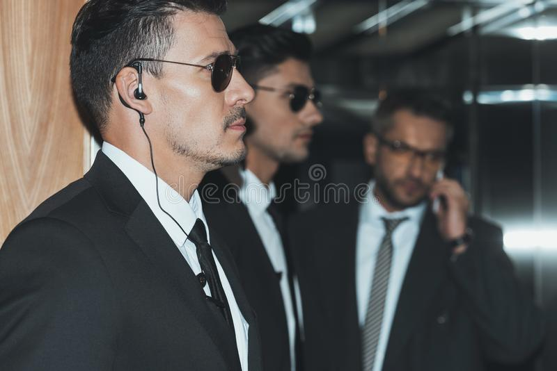 profile of bodyguards in sunglasses and businessman royalty free stock photos