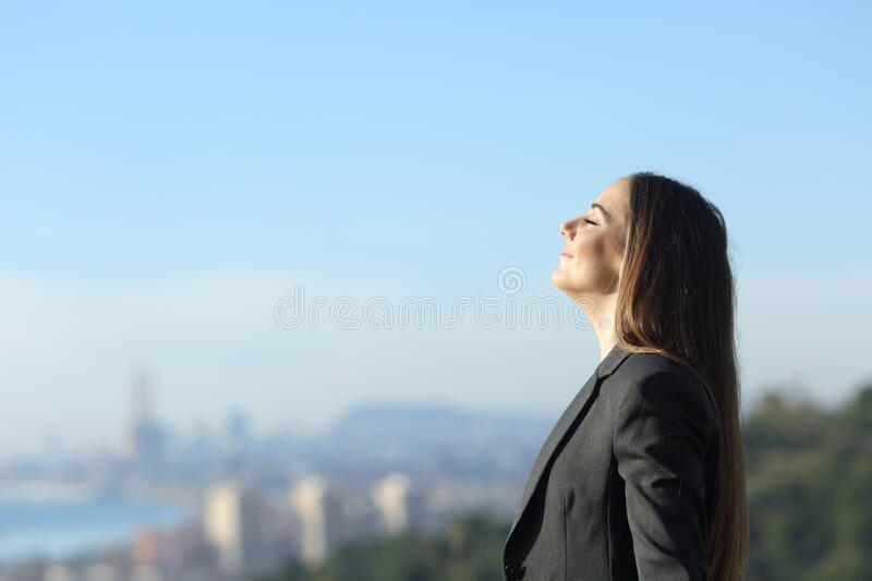 Profile of a businesswoman breathing fresh air stock photos