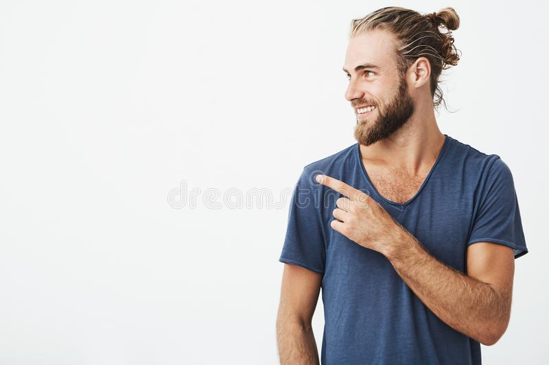 Profile of cheerful handsome man with fashionable hairstyle and beard smiling brightfully and pointing at free space for stock photography