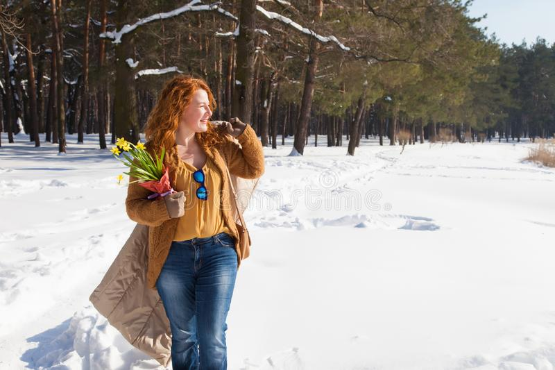 Profile of cheerful positive woman having peaceful stroll through forest snowdrifts royalty free stock photography