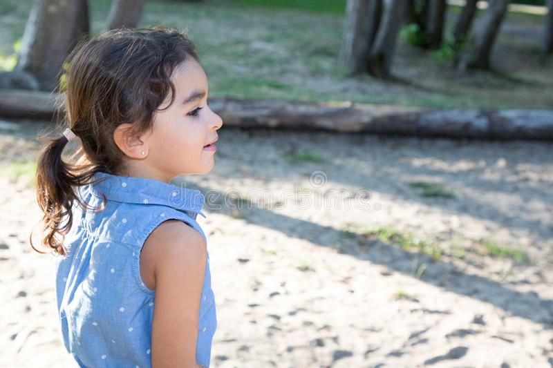 Profile child brunette girl outdoor in summer park royalty free stock photo