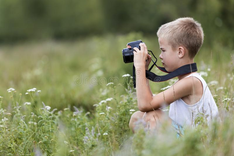 Profile close-up portrait of young blond cute handsome child boy with camera taking pictures outdoors on bright sunny spring or stock image