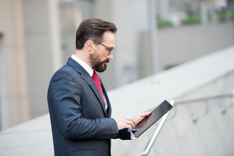 Profile of concentrated mature manager using a tablet in the street. Attentive concentrated bearded manager standing in the street while using digital tablet and royalty free stock photography