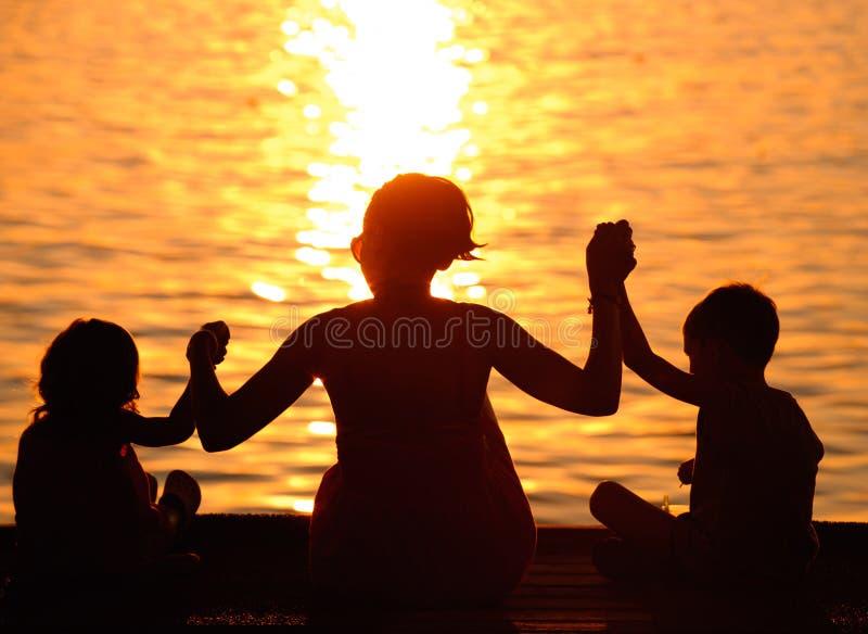 Profile der Mutter und der Kinder am Sonnenuntergang lizenzfreie stockfotos