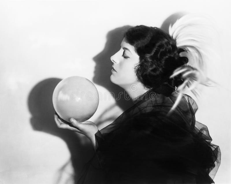 Profile of dramatic woman holding sphere stock image