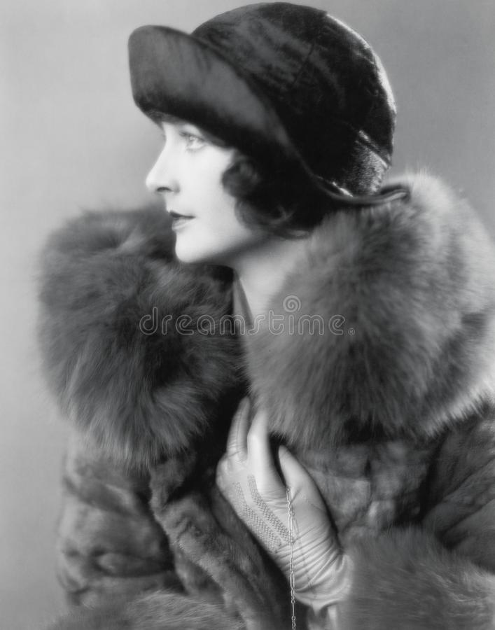 Profile of an elegant woman in a fur coat and satin hat royalty free stock photo