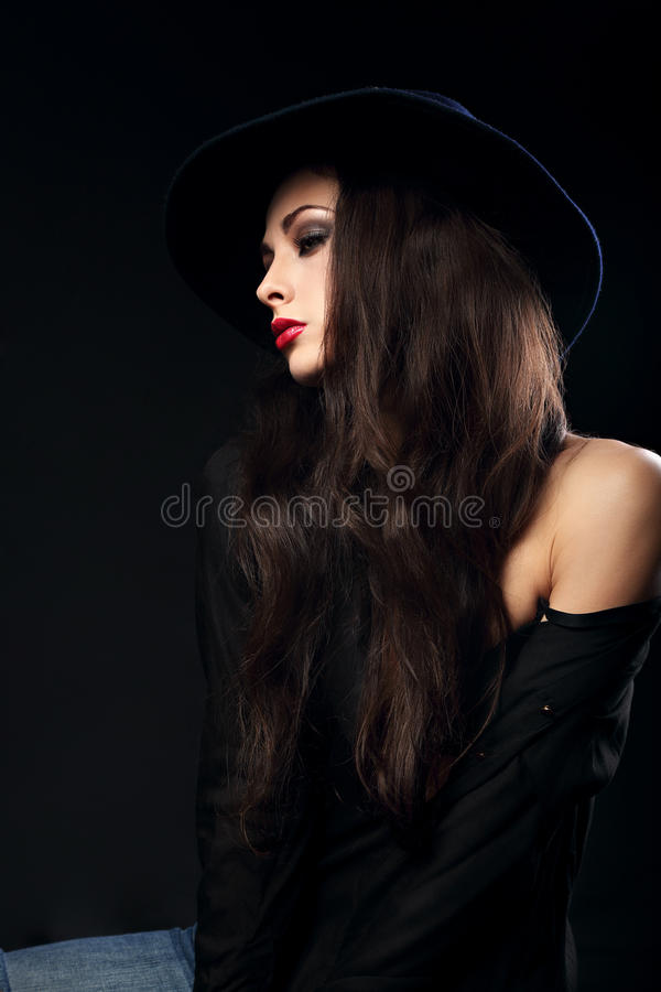 Profile of expressive female model posing in black shirt and elegant hat with red bright lipstick on dark shadow background. CLoseup portrait royalty free stock photography