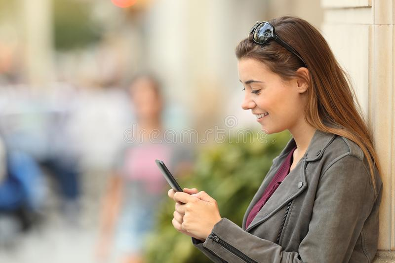 Profile of a fashion girl using a smart phone outside royalty free stock image