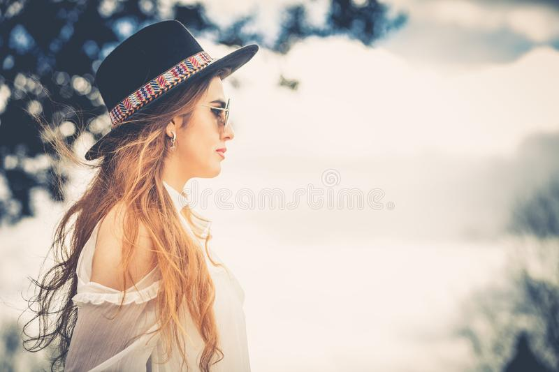 Profile of fashionable woman long hair with hat and sunglasses. Profile of a young fashionable woman with light brown long hair and with hat and sunglasses royalty free stock photo