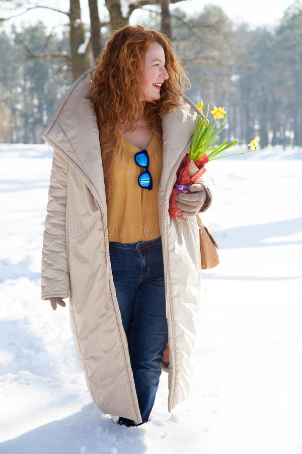 Profile of fashionable woman in warm clothes walking through snowdrifts stock image